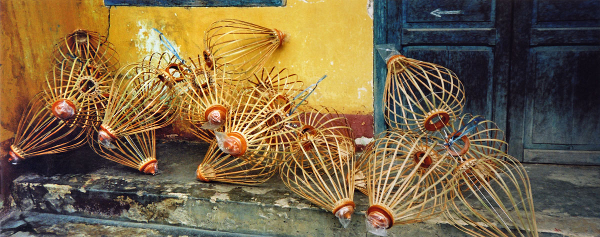 lantern 'skeletons' against a yellow wall in Hoi An, Vietnam
